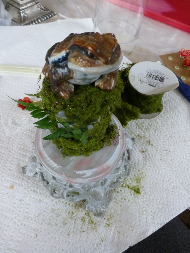 The toad gets glued onto the top of the moss-covered post, which is mounted to the wood base.