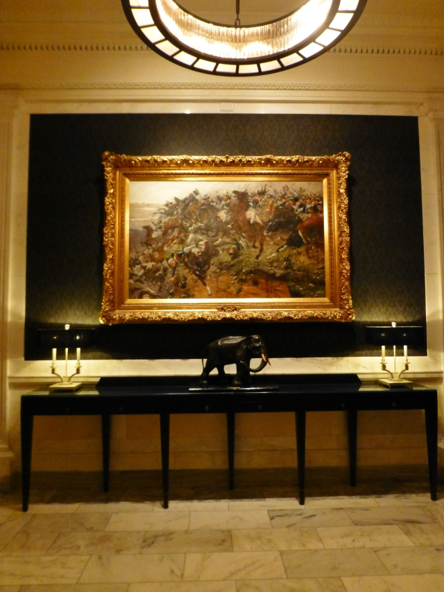 Amazing paintings, often depicting military scenes, fill the walls in every room and hallway. This one is outside of a more modern dining room.