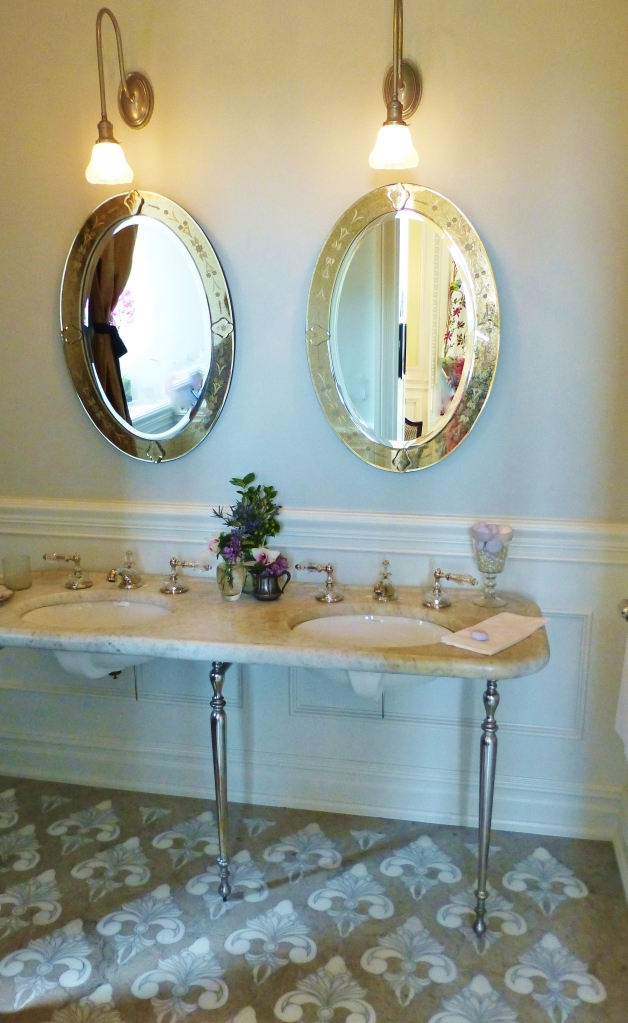 This serene powder room is just outside the office of the lady of the house.  The paneling is elegant, the colors are inviting, the lighting sparkles, and the accessories are beautiful.