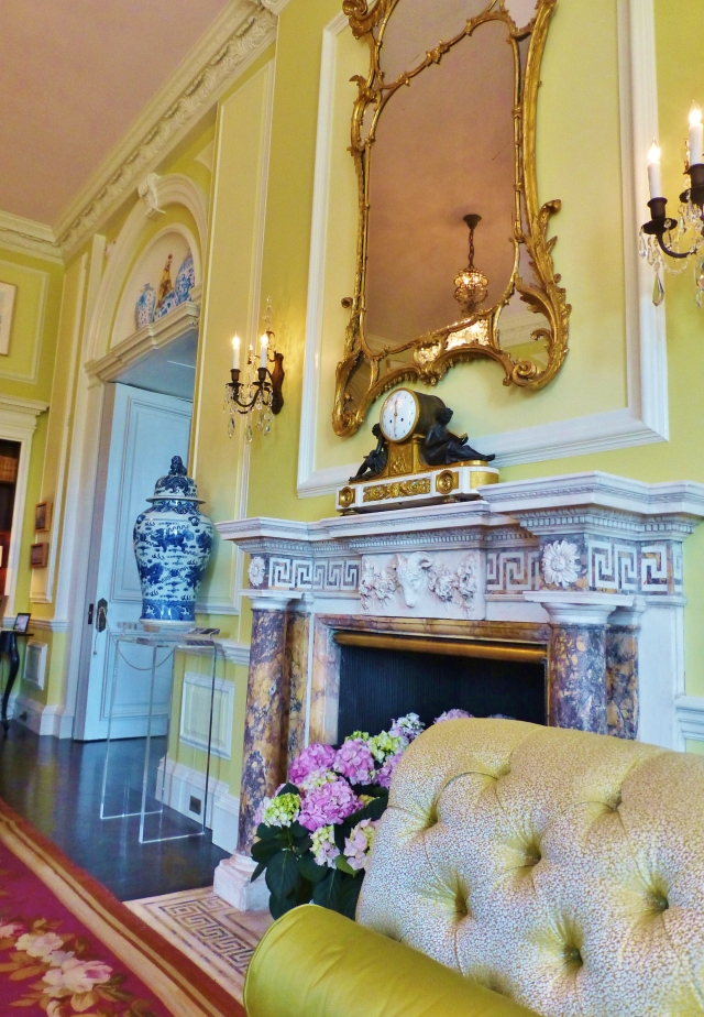 The original fireplace mantel shines when surrounded with this chartreuse green wall color and fabrics.  Blue and white porcelains are also a feature in the space.