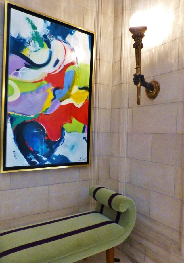 A colorful painting anchors this corner of Megan Young's grand entry space.  The velvet bench is so sculptural and elegant!