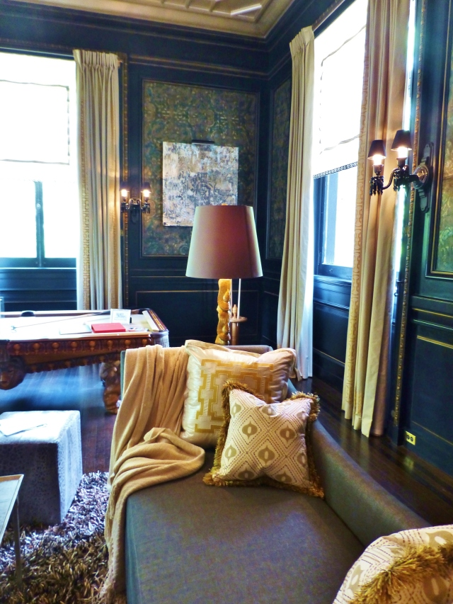 In this photo, you can appreciate how the light-colored draperies and pillows contrast beautifully with the dark walls.  The designer chose to use gold accents, which enhance the gold leaf detailing of the paneling in the room.  Notice the shaggy textured rug and brush fringe on the pillows--both of which update the space.