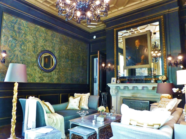 Luxurious finishes are found throughout this room, from the embossed leather wall-coverings, to the black paneling with gold-leafed details.  I love the mirrored over-mantel with a majestic portrait mounted on top!