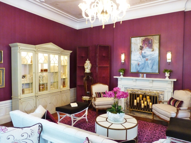 The merlot-colored walls have a strie effect, adding texture and interest to the strong coloring.  Bright white furniture provides high contrast.