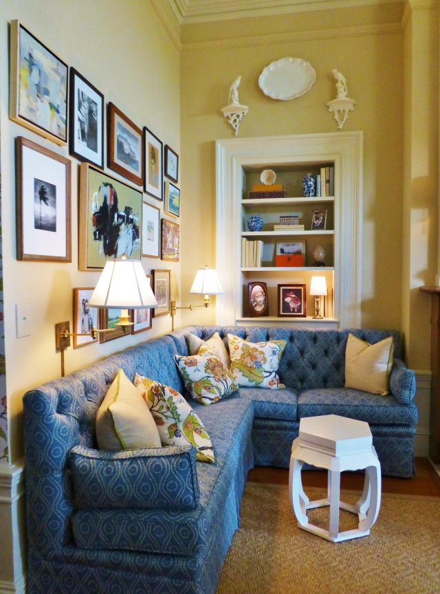 A blue tufted banquette anchors this corner near the entrance.  It has a well organized gallery art arrangement with beautifully practical wall-mounted lamps and a well-placed bookcase for keeping reading materials close at hand.