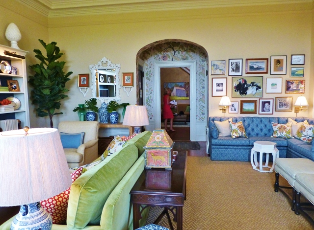 The entry alcove has wallpaper in the same pattern as the colorful pillows used throughout the room.  The designer did a great job of zoning the sitting areas in this space, with the main TV viewing area on the left and a custom banquette for lounging near the fireplace at the right.