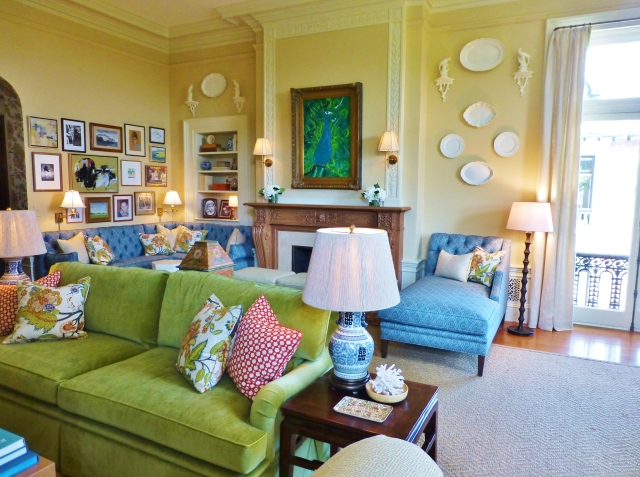 The floral pillows, seen here on the green sofa and blue tufted banquette, are the obvious color inspiration for the space.