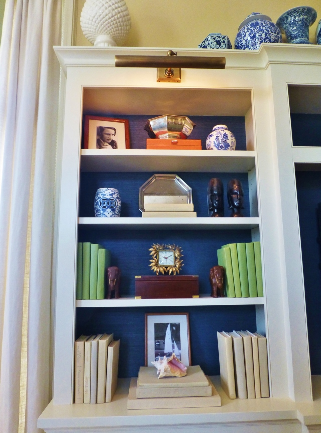 A detail of the cabinetry shows the artful arrangement of cherished objects.  The color-coordinated books are fabulous and the bold blue textured paper (grasscloth or possibly fabric?) looks terrific when placed in the back of the shelves.  Don't miss the beautiful library lights at the top of the shelves...I'm currently in the process of installing similar fixtures in my own home library!