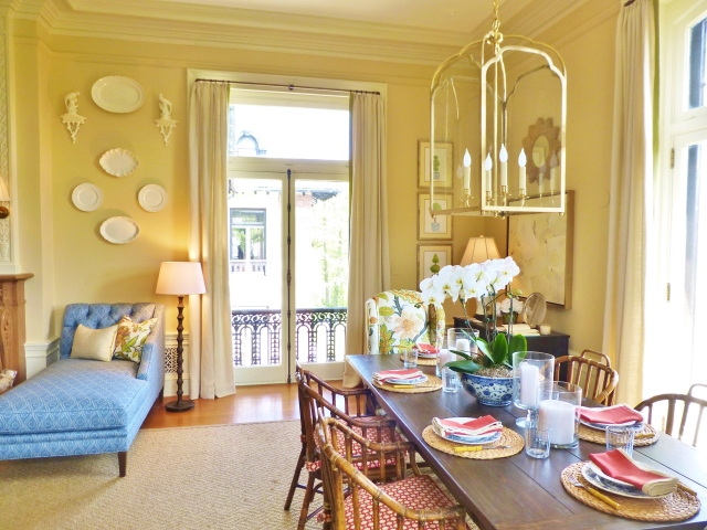 Here you can see the transition between the sitting area and the dining area.  Don't you just love how the creamware plates pop off the neutral wall color?  A large lantern is used as a chandelier above the planked farm-style table.