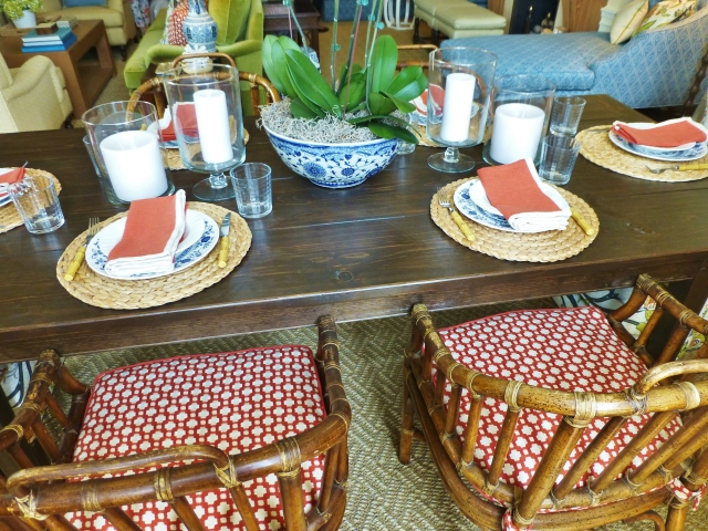 The rustic table is home to beautiful place settings.  Braided fiber mats repeat the natural feel of the sisal floor-covering, while elegant blue and white plates are the obvious choice for dinnerware.   Bamboo flatware and vintage rattan chairs also reflect the earthy casual feel of this room.