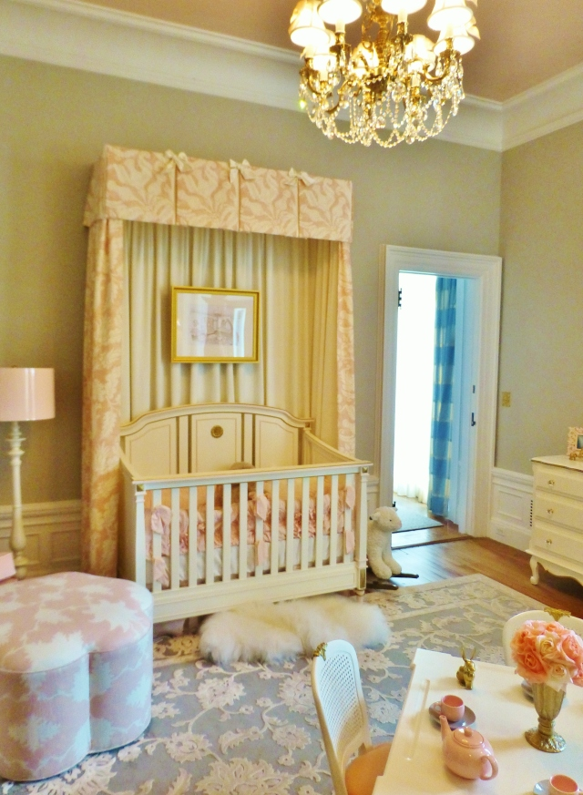 Bright white trim and a high-gloss blush ceiling are striking against the warm grey walls in this baby's room.