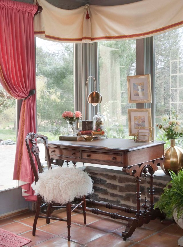 A handsome 19th century desk and chair are placed in the windows to allow for working while enjoying the view.  You can also see a close-up of the custom valances in this image.  The simple ivory linen-textured fabric is enhanced by a layered gold velvet and coral braid trim.  Starburst medallions and coral tassels are found at the junction of each soft swag.