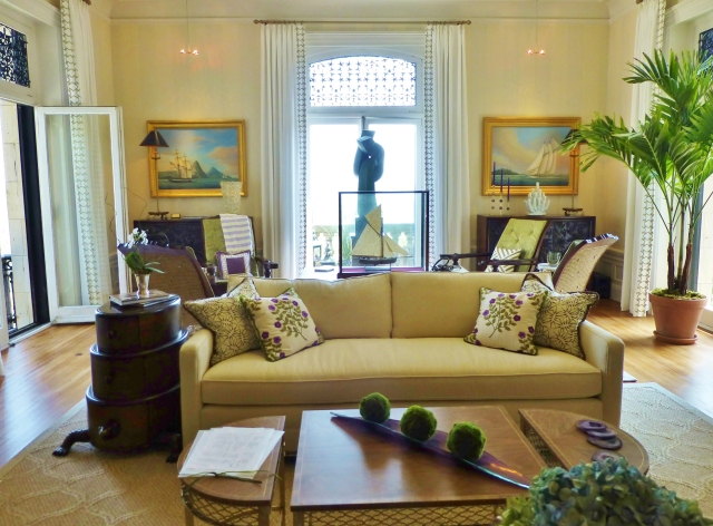 Upon entering the large living room, you are welcomed by a neutral transitional sofa with colorful embroidered pillows.  Notice the purple and green accents found throughout the room!  The extra tall windows are treated to simple white drapery panels with an embellished leading edge.