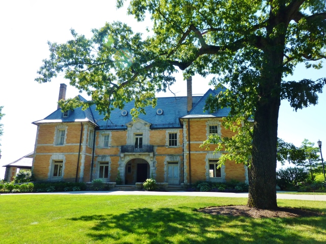 Seen here from the entrance drive, the mansion's symmetrical Beaux Arts style façade is framed by another mature tree in the foreground.  I just adore the light grey stone-work, contrasting with the joyful color of the yellow brick!