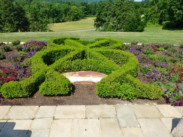 "This verdant knot garden overlooks the valley below the cathedral.  The inscription on the stone is from the book of Revelations in the Bible:  ""I am the Alpha and the Omega the Beginning and the End the First and the Last."""
