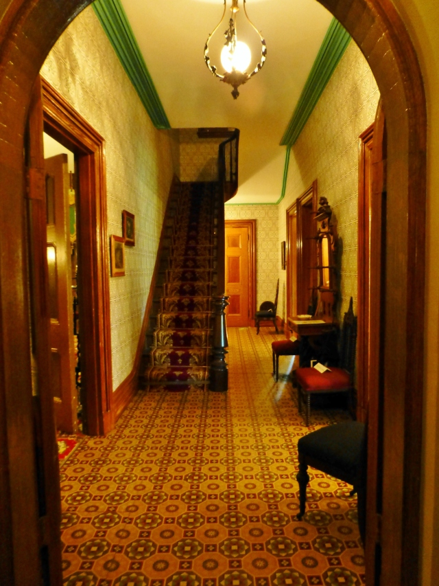 The entry hall of the Ebenezer Maxwell Mansion features true Victorian elements with lots of pattern.  Wallpaper is a prominent feature, as is the historically accurate linoleum floor (a Victorian innovation fabricated with Linseed Oil).  Also of note is the richly patterned stair runner with brass rods.