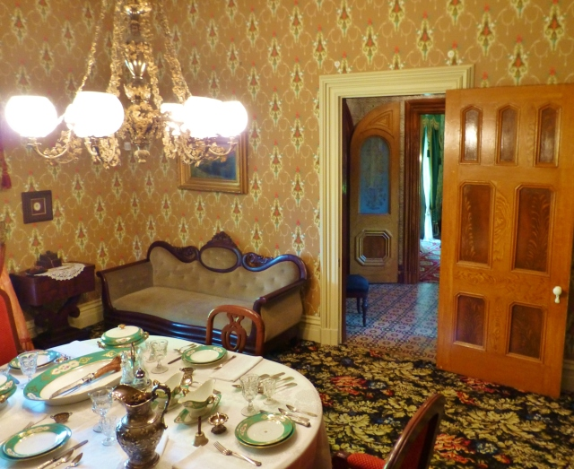 The dining room features a Scalamandre wallpaper, authentic to the period.  The table is set with a fine tablecloth and formal place settings.  I'm sure you know the Victorians dearly loved their silver and china.  Me too!