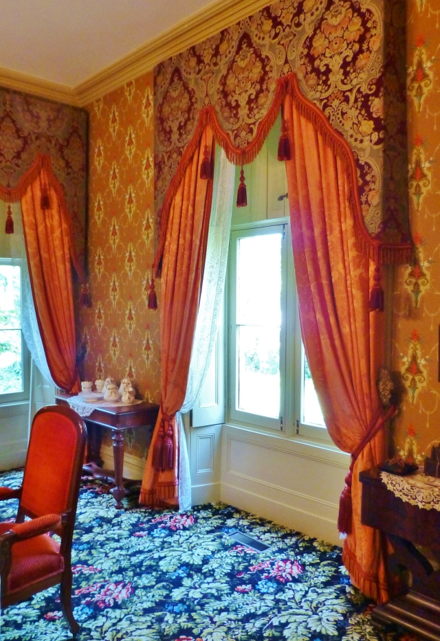 The dining room windows feature silk draperies with ornate damask lambrequins.  A lambrequin is an upholstered cornice board which extends farther down the side of the window.  These lambrequins are enormous!  Can you see how big they are compared with the dining chair?