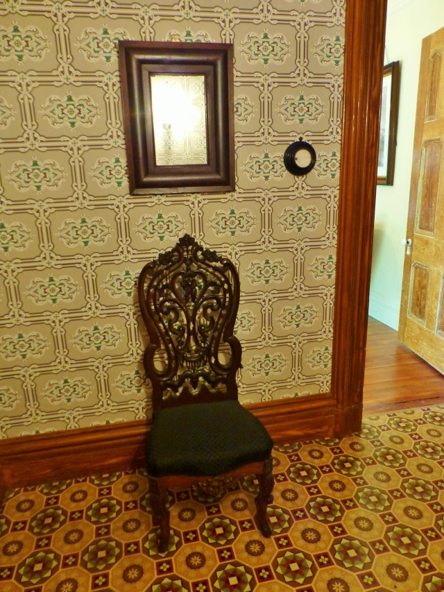 All the way at the back of the foyer sits this lovely chair with an ornately pierced floral back.   Notice the black horsehair upholstery, typical of chairs in this period.  Above the chair is an antique mirror and to the right, you will see a round circle on the wall.  Let's look at that in more detail.