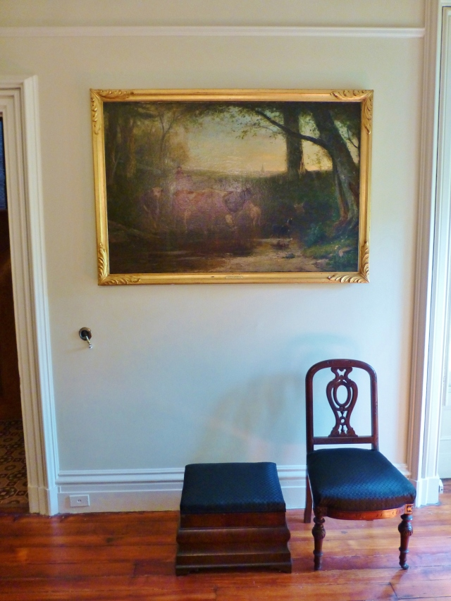The opposite side of the room is very simple.  A large landscape oil painting and a chunky Empire style ottoman and side chair.  My eye is drawn to the crank in the wall...do you see it there on the left?  It's for calling the maids!