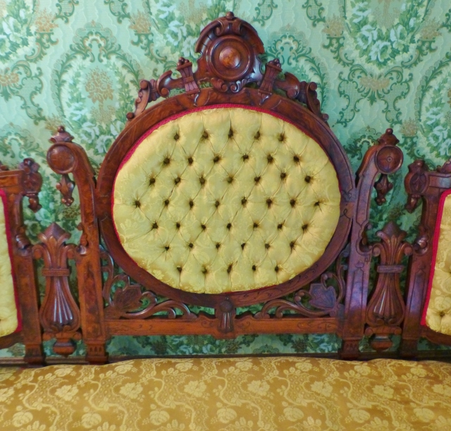 The Renaissance Revival settee in this photo has such amazing carved details and is one of a pair found in the parlor, along with some matching chairs.  These are such sculptural pieces of furniture.  The cheerful yellow upholstery really brightens the dark (but beautiful), heavily carved wood.