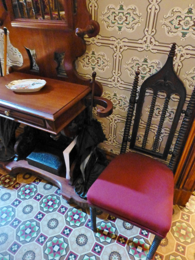 Flanking the Hall Tree are a pair of lovely Victorian Gothic Revival chairs.  These are fabulous examples of this quintessentially Victorian furniture.  Don't you just love all the spool turning--so exotic! This image also shows a better close-up of the geometric pattern in the linoleum floor, and the 'Ashlar Block' style wallpaper that was so popular at the time this home was built.
