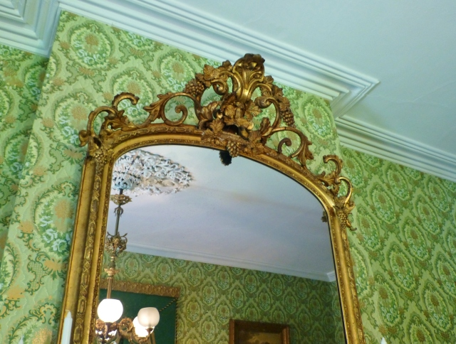 The glorious gilt mirror above the fireplace mantel goes all the way to the crown moulding.  It is adorned with ornate scrolls and sculpted grapes.  Reflected in the mirror is the equally ornate plaster ceiling medallion from which the chandelier is suspended.