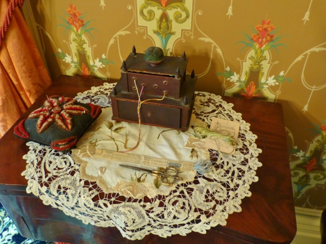 The dining room also features a sewing corner, with various implements that might be used by the lady of the house.  I'm very fond of the thread holder in this image, which kept all the different colors of embroidery floss from getting tangled up.