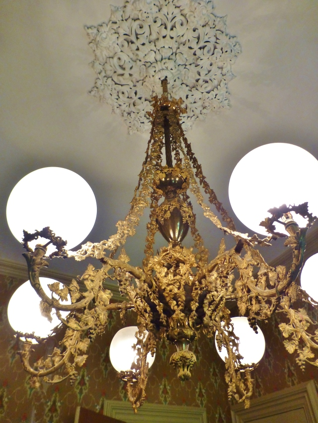 The lavish dining room chandelier is dripping with grapes and grapevines.  Each arm is a faux-bois marvel, emulating wood with grapevines twirling around their length.