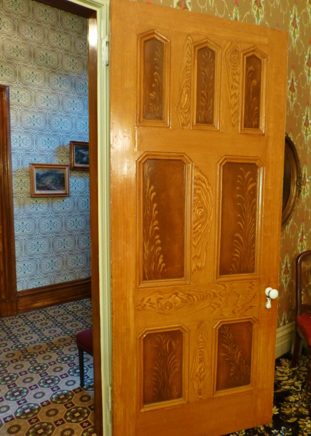Much of the woodwork in the house, including the doors in the dining room are hand-painted faux wood grain.  If you look closely you can see that various colors of brown, caramel and gold paint have been used to simulate more expensive wood grain patterns.  This was a popular thing to do in middle class homes of the Victorian era. Doesn't it look so real?