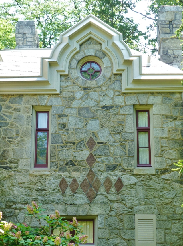 This part of the house features an ocular window at the top.  Here you can also see the decorative red stone-work featured in several locations on the exterior.  It reminds me of the argyle pattern, made up of several diamonds or lozenges.