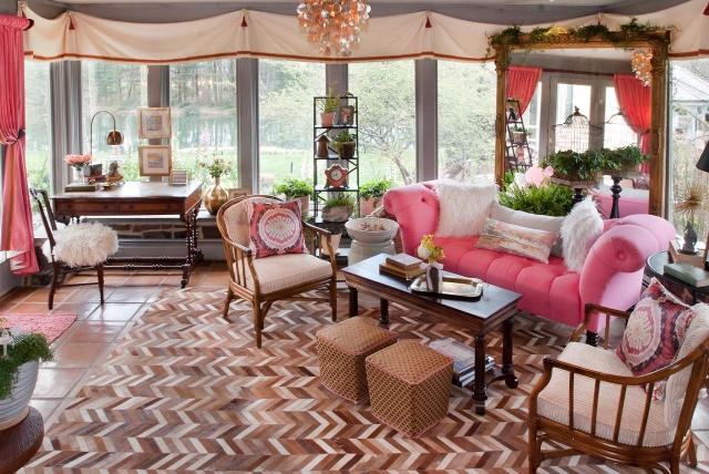 Sunroom with Vintage Vavoom Bold coral accents are found throughout this eclectic sunroom, along with a statement rug made of cowhide in a chevron pattern.  Three centuries of antiques are represented in the space.