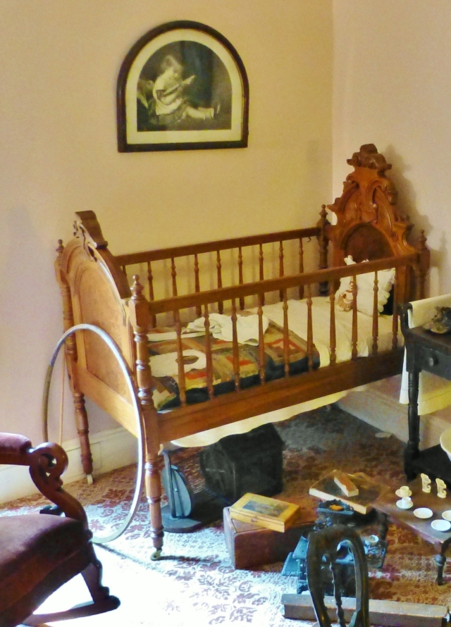Notice the stick and hoop at the foot of the crib...this was a popular Victorian child's diversion as were the other toys scattered across the floor.  Beneath the crib is an antique squirrel cage--children would often keep squirrels as pets and enjoyed observing them running on the wheel, like hamsters.