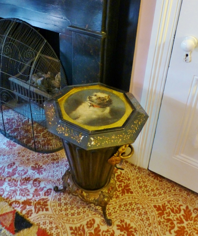 Check out this coal bin sitting by the hearth in the children's bedroom.  Decorative coal bins are containers to store coal for your fireplace or stove.  Since a bucket full of coal sitting out in full view isn't all that attractive, the Victorians devised coal bins that hold a substantial amount of fuel at the ready, yet the containers also serve as a decorative element in the room.  This one features a precious dog portrait on the embellished octagonal top.