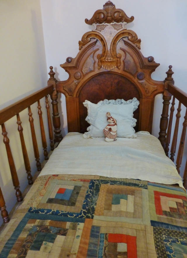 Here's a detail shot of the beautiful Renaissance Revival style crib.  I admire the hand-made baby quilt and fine linens.