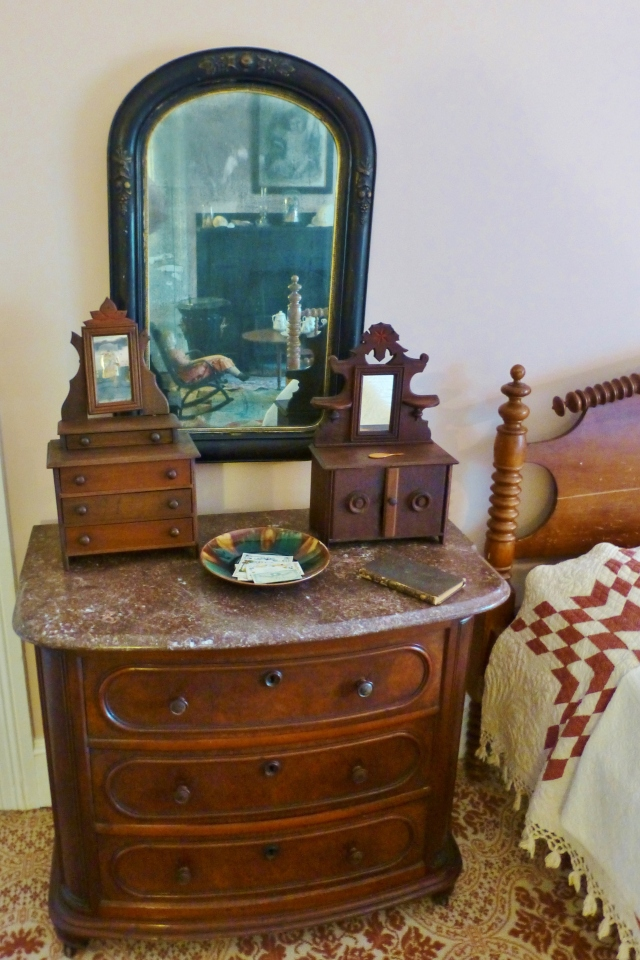 To the left of the bed is another pretty dresser, this one with a marble top.  On the dresser sits two miniature dressers.  This doll-sized furniture (along with salesmen's samples) is quite collectible today.  Aren't they adorable?!