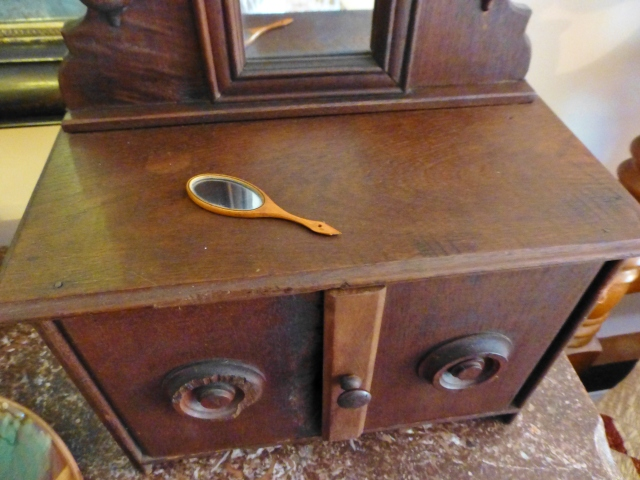 Even more cute is this very tiny hand mirror atop a miniature dresser!