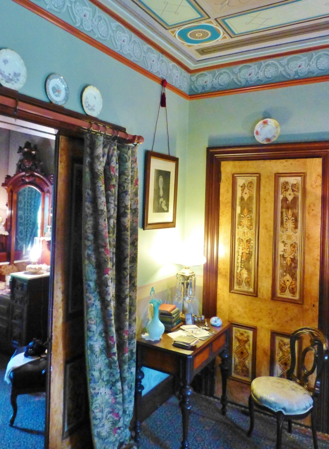 In a corner near the entry to the bedroom, sits a small desk and chair.  This photo shows a door with handpainted woodwork featured in the lounge.  You'll also notice the draperies on the pocket door.  These are called Portieres and, in addition to being decorative, helped to further divide and provide insulation between the spaces.