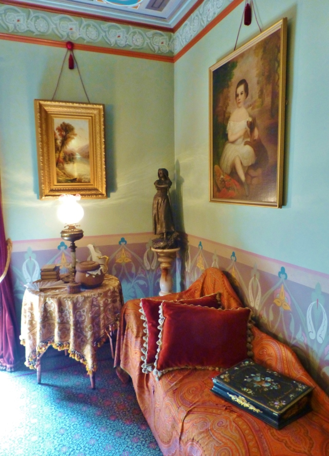 The lounge portion of the space has a papier-mache lap desk on the chaise for writing letters or composing poetry.  The luxuriously draped table contains books and sewing implements...appropriate lady-like activities.