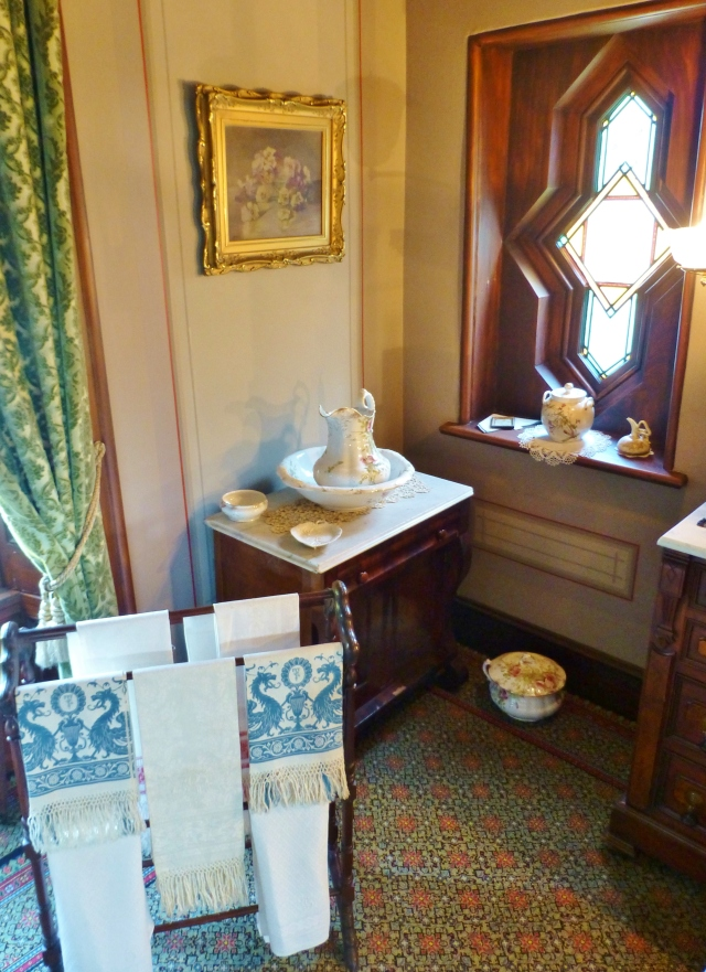 At the far corner of the bedroom, to the left of the vanity, sits a wash-stand with a bowl and pitcher.  This was a necessity in a house with no bathrooms!  Speaking of which...can you see the chamber pot beneath the window?  My father always calls them 'thunder mugs'.