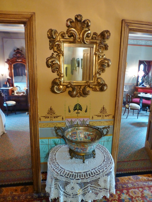 Back in the upstairs hallway, a stunning Italian-style gilded mirror welcomes you between the entrances of the two room suite.  From this vantage point (exiting the Children's room, behind you) the bedroom is at the left and the lounge at the right.  Notice the handpainted wainscoting behind the lace-covered table.  You'll also notice the layering of patterns with the area rugs in this image.