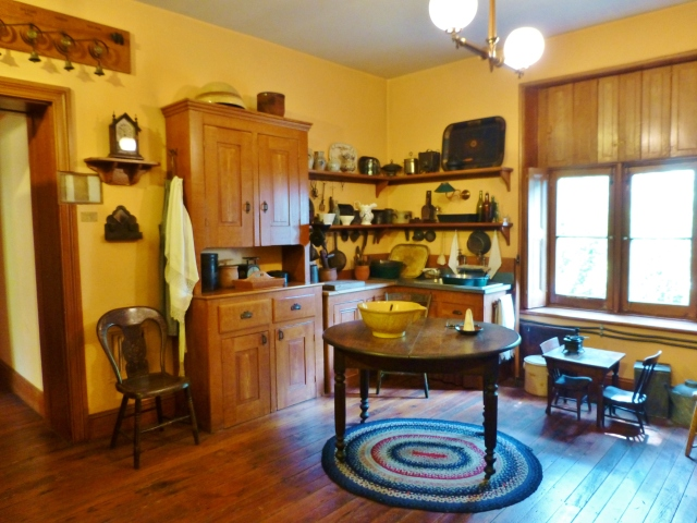 If you turn around and look back towards the hallway, you'll see the sturdy kitchen table with useful shelving and cupboards on the wall above.  Notice the cute little children's table and chairs by the window.