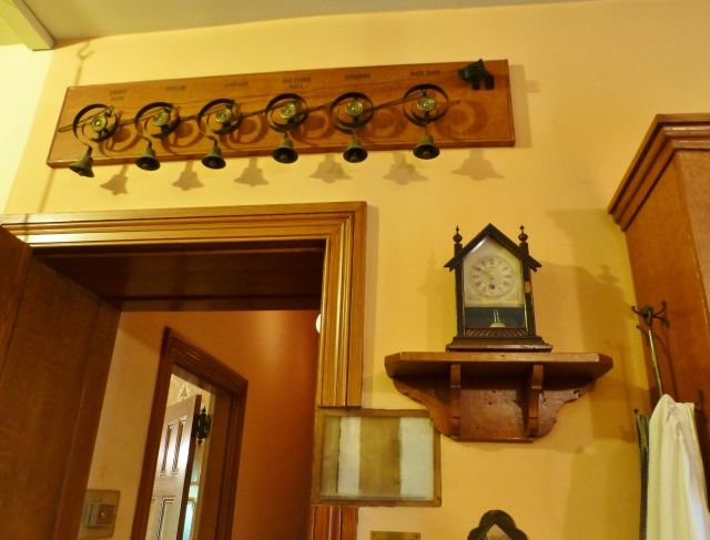 I just love this little steeple clock on a shelf in the kitchen--I collect antique clocks, myself, and this one is a beauty!  Notice the very interesting device above the doorway to the hall:  the servant call system, or house bells.