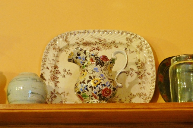 The open shelving contains many pretty and useful objects like the Stoneware platter and jug seen here.