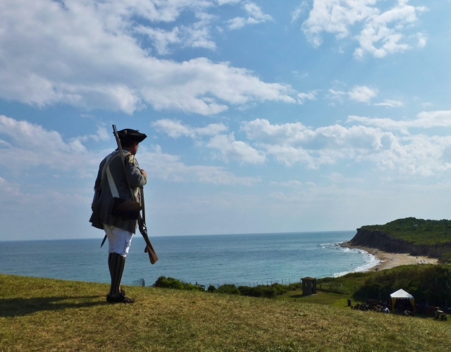 A gentleman in historic garb from the 1700's, holding a musket, looks out at the craggy shoreline from the Montauk Point Lighthouse.