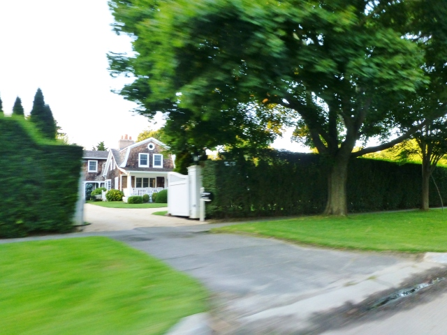A lovely shingle-style mansion peeking through the driveway-sized opening in a tall hedge is typical of The Hamptons.