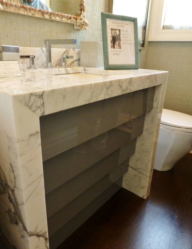 The vanity in the powder room was made with a waterfall-style marble top and had this interesting gray stepped front.  This sink base is very sleek and clean-lined.