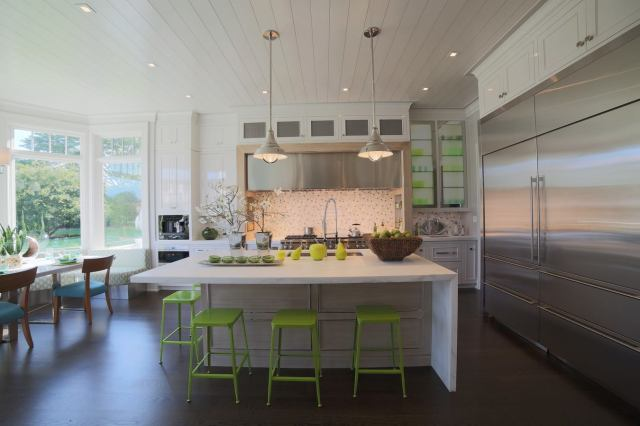 This photo can be found on the Ciuffo Cabinetry Facebook Page.  It shows the green stools tucked under the waterfall countertop at the island, and the full layout of the kitchen and breakfast area.
