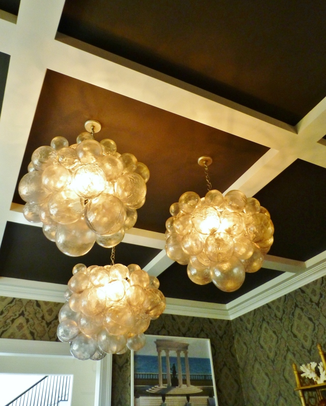 The cluster of three large bubble-like chandeliers draws you eye to the dramatically dark-painted coffered ceiling.