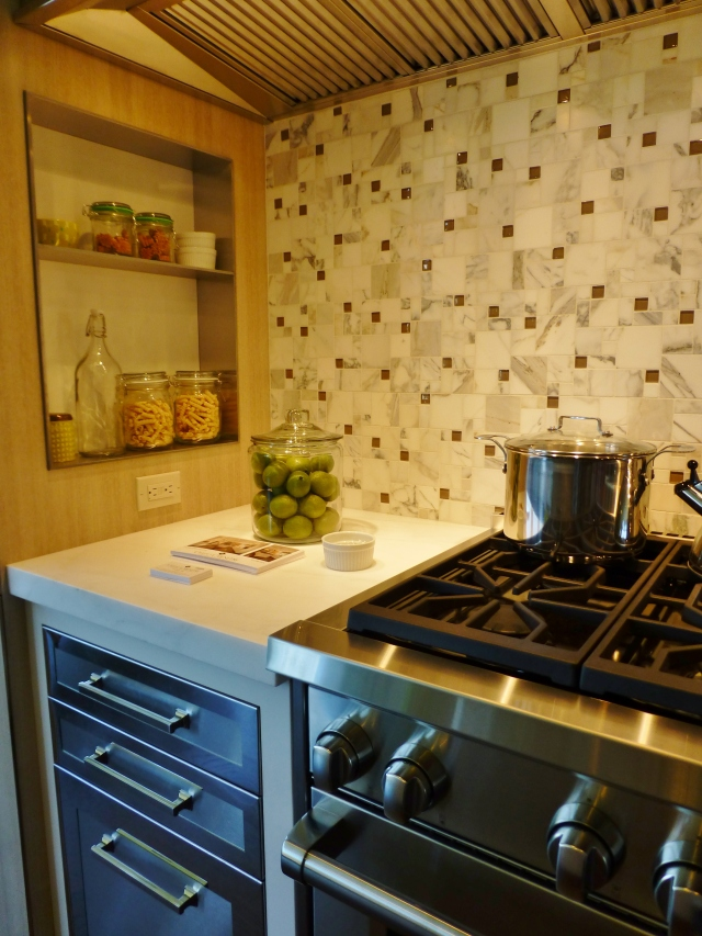 The gas stove is placed in an alcove to the right.  Isn't this mosaic marble backsplash pretty?
